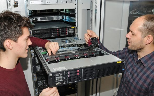 Together with his instructor, an apprentice computer scientist replaces a ventilator in a server.