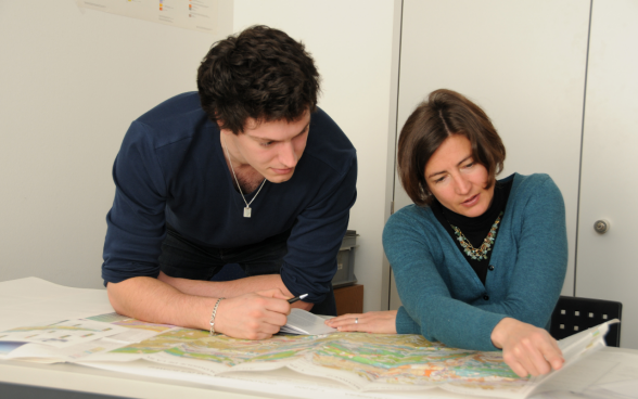 A graduate intern studies a geological map together with his supervisor